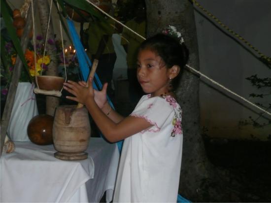 Niña maya preparando chocolate para tomar.