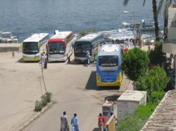 Les cars de touristes attendent proche de l'embarcadère du ferry.