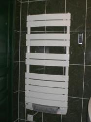 un sèche serviette électrique et soufflant est placé derrière la porte pour un gain de place