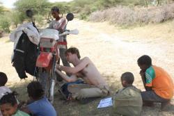 Etienne reparant sa moto sous l oeil intrigue des enfants